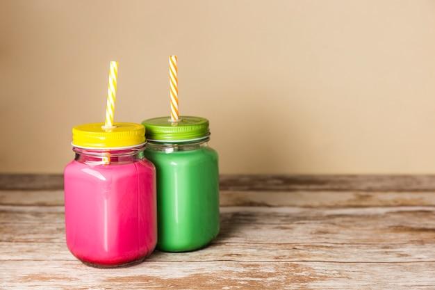 Vista frontal coloridos batidos en frascos con espacio de copia