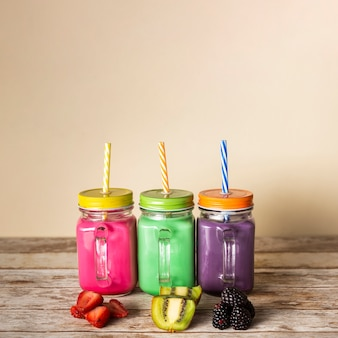 Vista frontal coloridos batidos en frascos con frutas