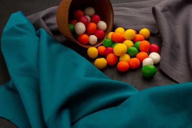 Vista frontal coloridos dulces dulces dentro de una olla marrón sobre el tejido gris y azul y oscuro