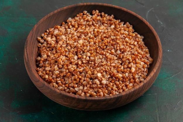 Vista frontal comida sabrosa de trigo sarraceno cocido dentro de la placa marrón sobre la superficie verde oscuro