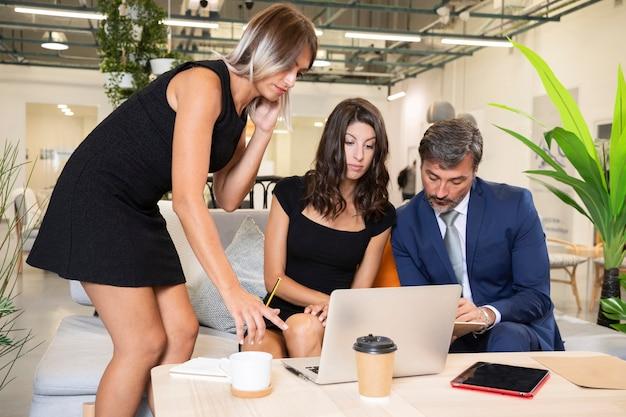Vista frontal de compañeros de trabajo que trabajan en la computadora portátil