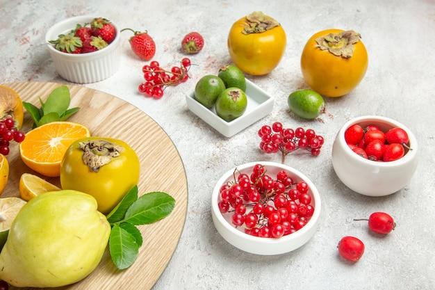 Vista frontal de la composición de la fruta diferentes frutas en la mesa blanca color baya fresca madura