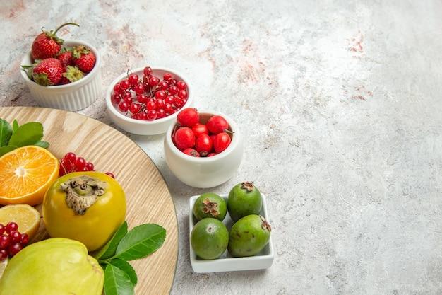 Vista frontal de la composición de frutas diferentes frutas en mesa blanca baya fruta fresca madura