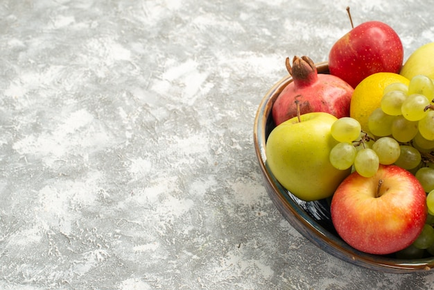 Vista frontal de la composición de frutas frescas manzanas, uvas y otras frutas sobre el fondo blanco fruta fresca suave color maduro vitaminev