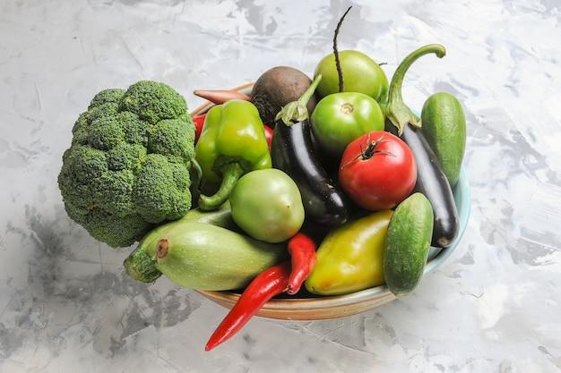 Vista frontal de la composición de verduras frescas dentro de la placa en la mesa blanca ensalada fresca madura