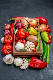 Vista frontal de la composición de verduras frescas en ensalada de mesa gris color maduro fresco
