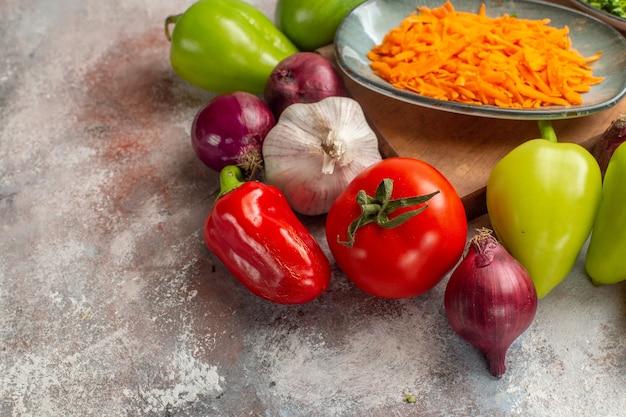Vista frontal de la composición de verduras frescas en el fondo blanco color de la comida vida sana ensalada de dieta madura