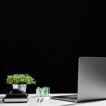 Vista frontal de la computadora portátil y la agenda en la mesa