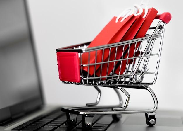 Vista frontal de la computadora portátil con carrito de compras y bolsas para el cyber monday