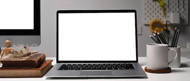 Vista frontal de la computadora portátil en el espacio de trabajo del diseñador creativo. pantalla en blanco para su información.