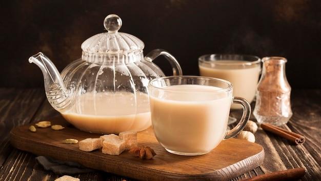 Vista frontal del concepto de té con leche en la mesa de madera
