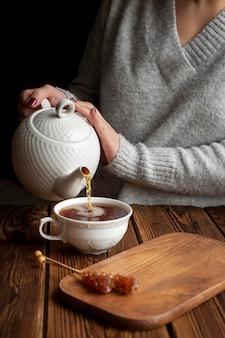 Vista frontal del concepto de té vertiendo mujer