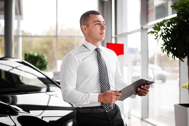 Vista frontal del concesionario de automóviles macho con portapapeles