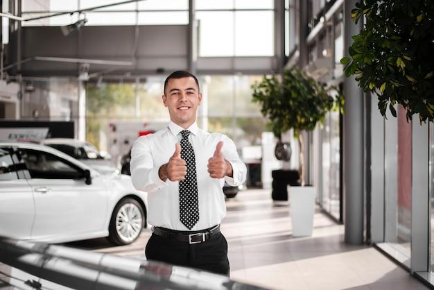 Vista frontal concesionario de automóviles masculinos mostrando signo ok