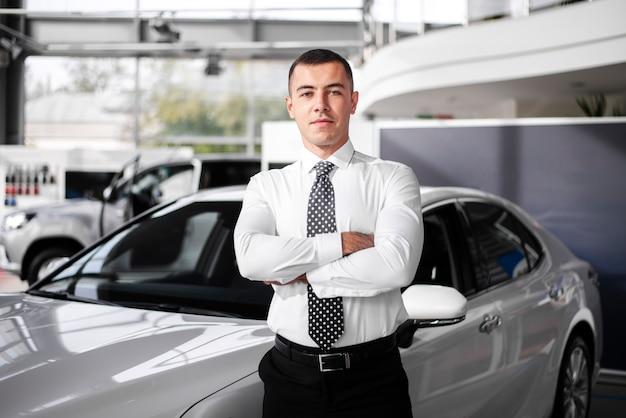 Vista frontal concesionario de automóviles masculinos de pie con los brazos cruzados
