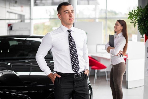 Vista frontal de concesionarios de automóviles compañeros de trabajo en la oficina