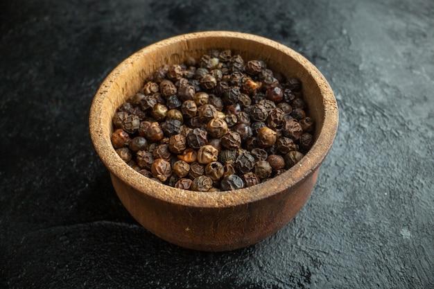 Vista frontal de los condimentos secos dentro de la placa en la comida picante de pimienta oscura