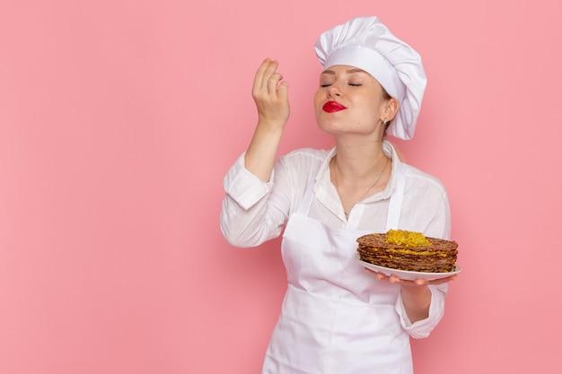 Vista frontal confitería femenina en ropa blanca sosteniendo deliciosos pasteles en la pared rosa trabajo de pastelería dulce confitería trabajo