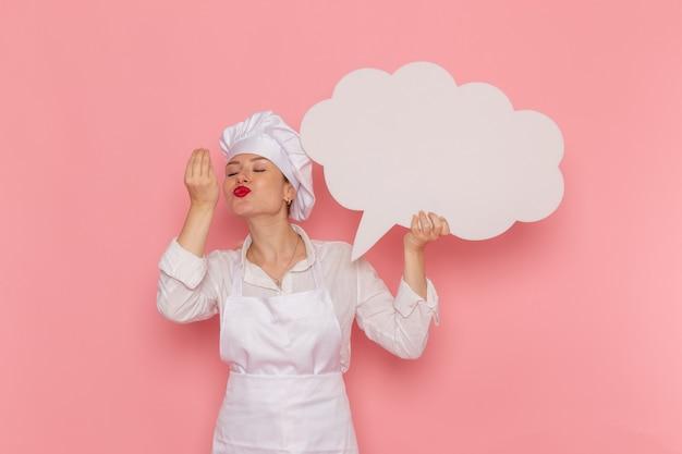 Vista frontal confitero femenino en ropa blanca con gran cartel blanco en la pared rosa cocinar trabajo cocina cocina comida