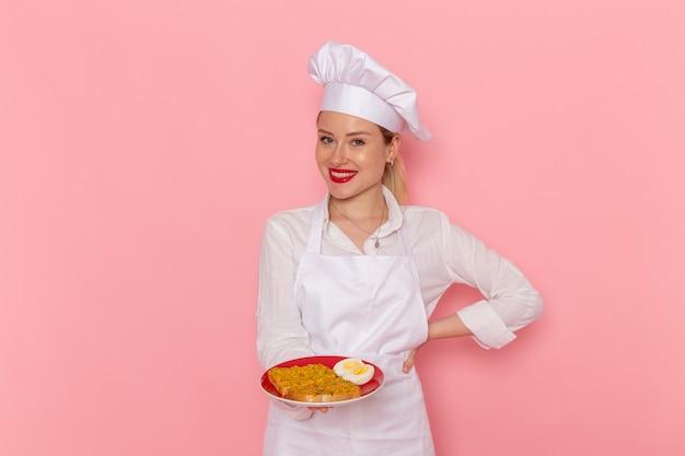 Vista frontal confitero femenino en ropa blanca sosteniendo un plato con comida en la pared rosa cocinar trabajo cocina cocina comida