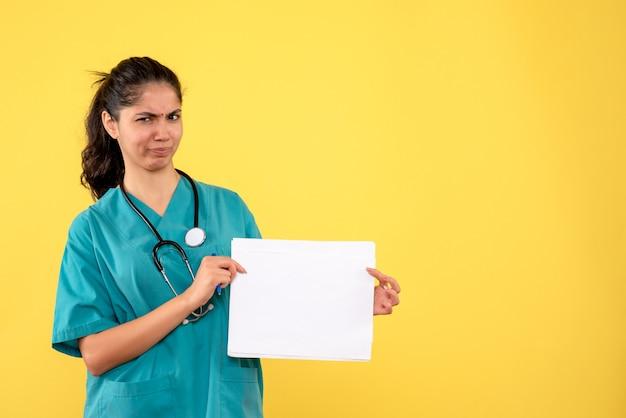 Vista frontal confundida doctora sosteniendo papeles sobre fondo amarillo