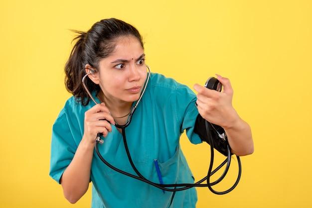 Vista frontal confundida joven doctora con esfigmomanómetro sobre fondo amarillo
