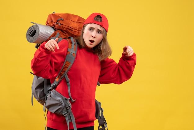 Vista frontal confundida viajera con mochila apuntando al suelo