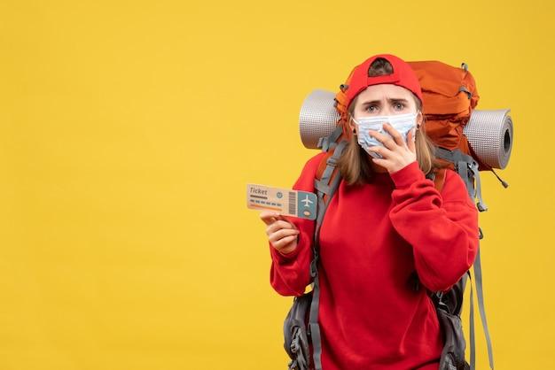 Vista frontal confundida viajera con mochila y máscara con boleto de avión