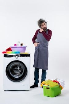 Vista frontal confundido hombre ama de llaves poniendo la mano en el bolsillo de pie cerca de la lavadora blanca sobre fondo blanco.