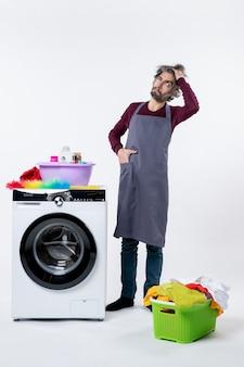 Vista frontal confundido hombre ama de llaves poniendo la mano en el bolsillo de pie cerca de la lavadora sobre fondo blanco.