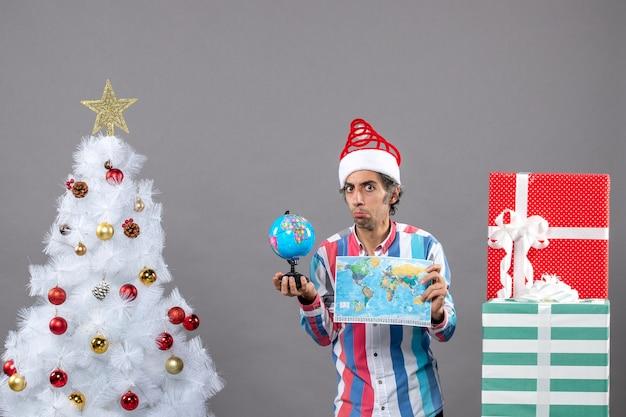 Vista frontal confundido hombre sosteniendo globo y mapa del mundo