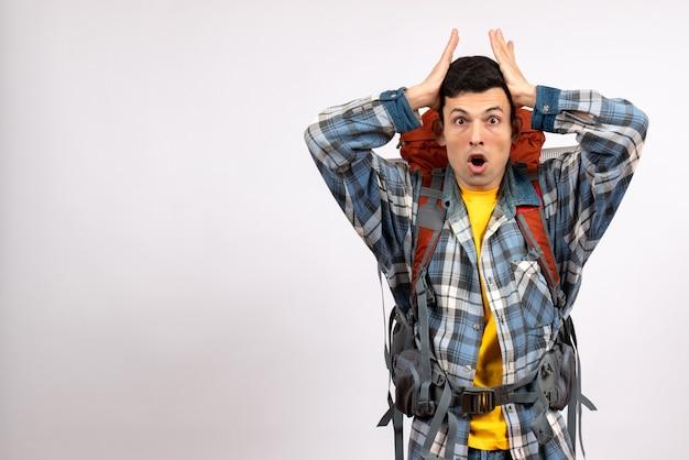 Vista frontal confundido joven viajero con mochila sosteniendo la cabeza