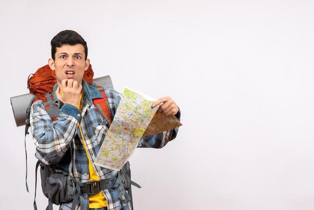 Vista frontal confundido joven viajero con mochila sosteniendo mapa