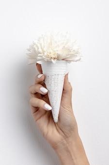 Vista frontal del cono de helado de mano con flor
