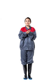 Vista frontal del constructor femenino en uniforme especial aplaudiendo en la pared blanca