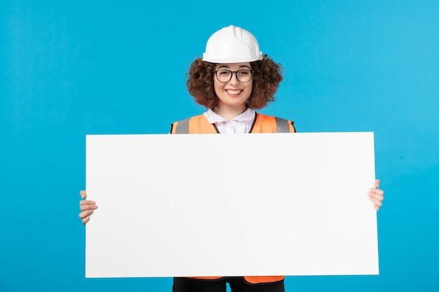 Vista frontal del constructor femenino en uniforme sosteniendo escritorio liso blanco sobre pared azul
