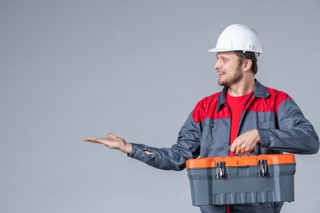 Vista frontal del constructor masculino en caja de herramientas de sujeción uniforme sobre fondo gris