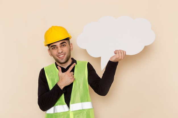 Vista frontal del constructor masculino en casco amarillo con gran cartel blanco y posando sobre fondo claro