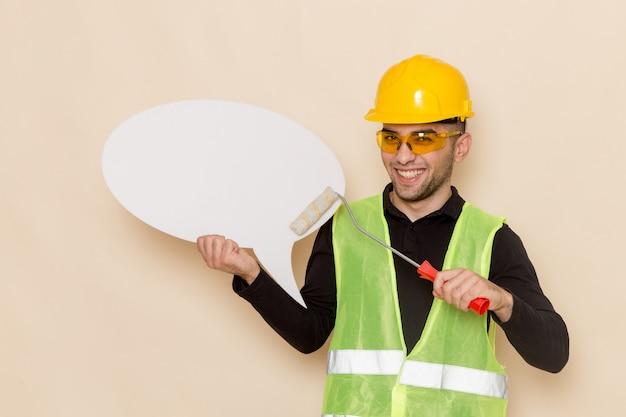 Vista frontal del constructor masculino en casco amarillo con pincel y cartel blanco sobre fondo claro