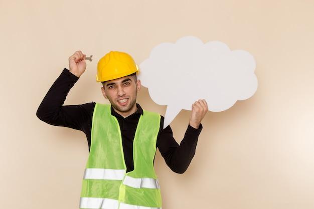 Vista frontal del constructor masculino en casco amarillo sosteniendo la herramienta y cartel blanco sobre fondo crema