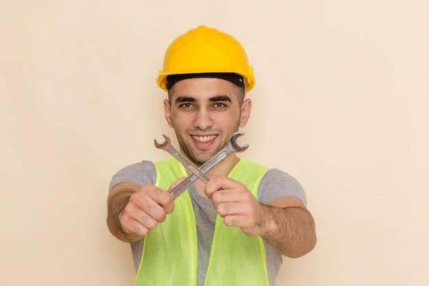 Vista frontal del constructor masculino en casco amarillo sosteniendo la herramienta plateada y sonriendo sobre el fondo claro