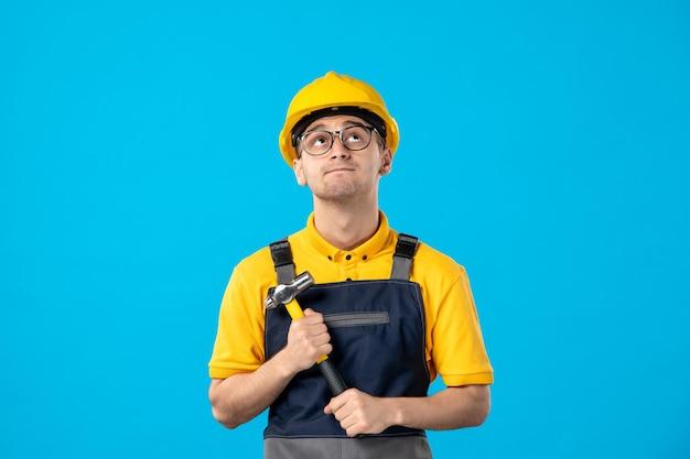 Vista frontal del constructor masculino de pensamiento en uniforme con martillo en azul