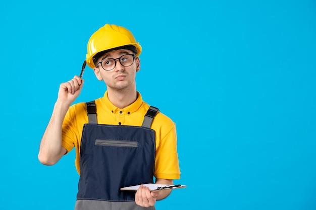 Vista frontal del constructor masculino de pensamiento en uniforme con nota de archivo en azul