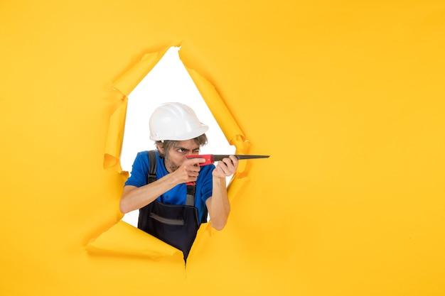 Vista frontal del constructor masculino sosteniendo el taladro sobre fondo amarillo