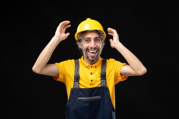 Vista frontal del constructor masculino en uniforme amarillo emocionado en la pared negra