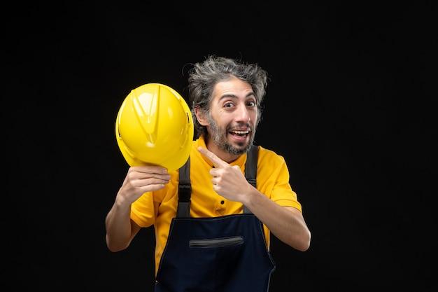 Vista frontal del constructor masculino en uniforme amarillo en la pared negra