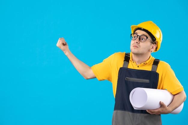 Vista frontal del constructor masculino en uniforme amarillo con plan de papel en azul