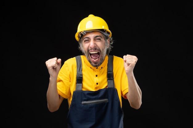 Vista frontal del constructor masculino en uniforme amarillo regocijándose en la pared negra