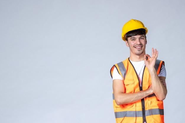 Vista frontal del constructor masculino en uniforme y casco amarillo en la pared blanca