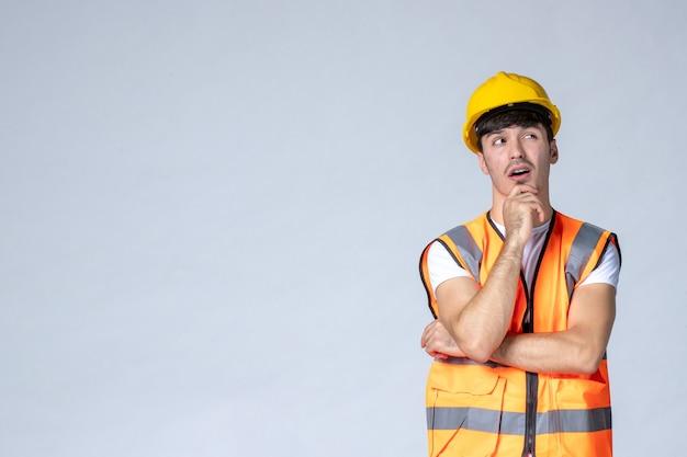 Vista frontal del constructor masculino en uniforme y casco amarillo pensando en la pared blanca